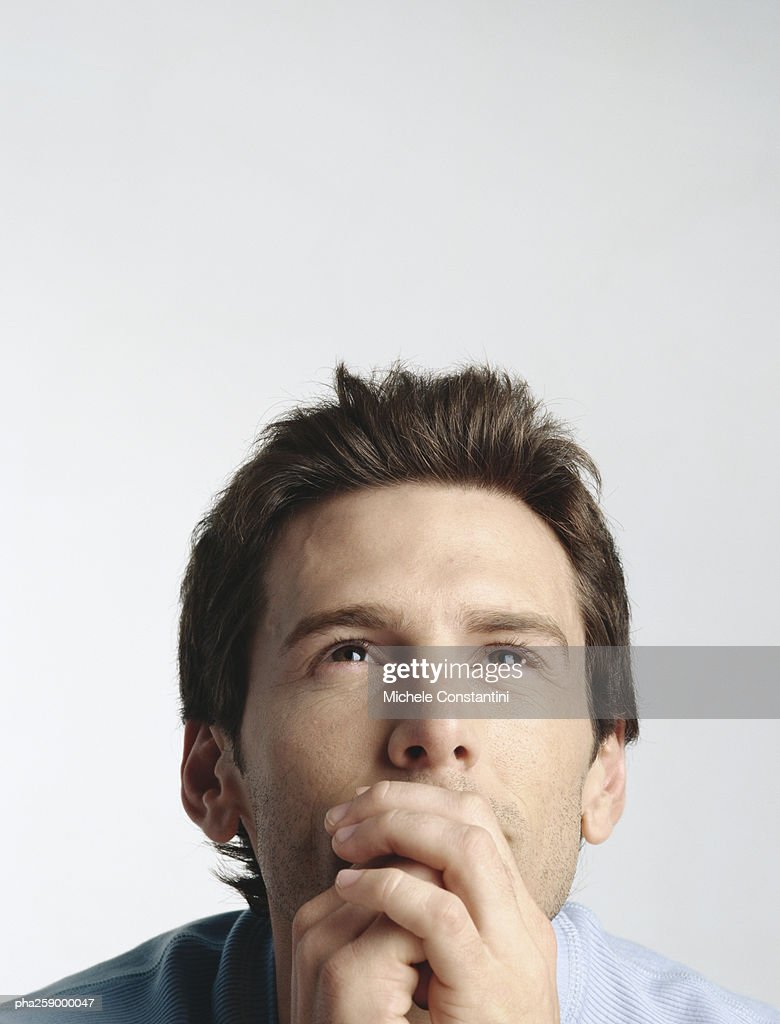 Young man with hands clasped in front of mouth, looking up : Stockfoto