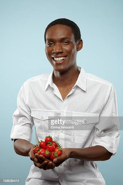 young man with hands full of strawberry