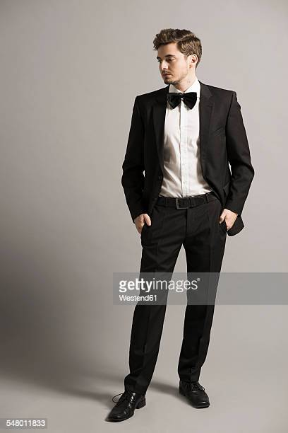 young man with hands in his pockets wearing black suit, white shirt and bow - evening wear stock pictures, royalty-free photos & images