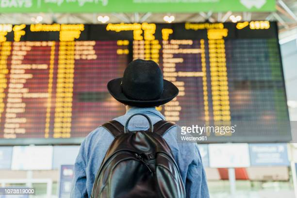 young man with hat and backpack looking at arrival departure board at the airport - estrada da vida imagens e fotografias de stock