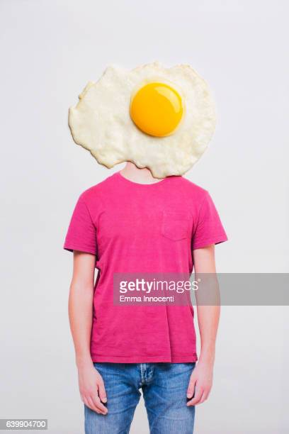 Young man with head covered by fried egg