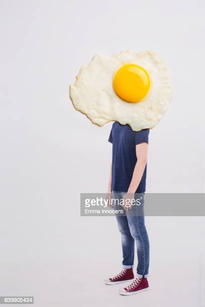 Young man with head covered by large fried egg