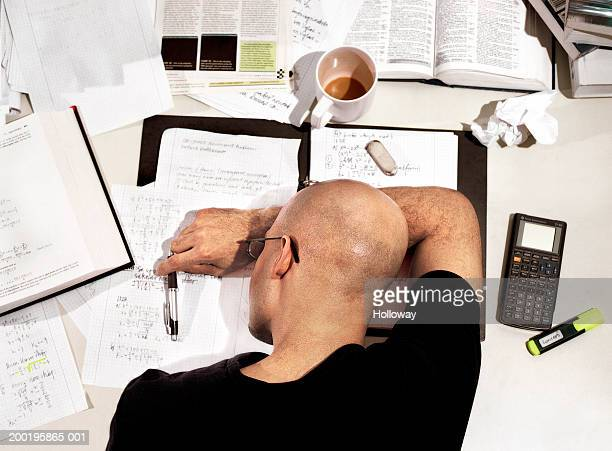 Young man with head down on desk covered in text books and paperwork