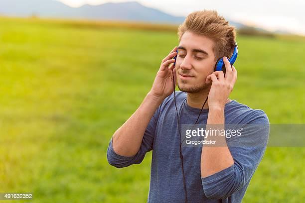 Junger Mann mit Kopfhörer Musik hören im park