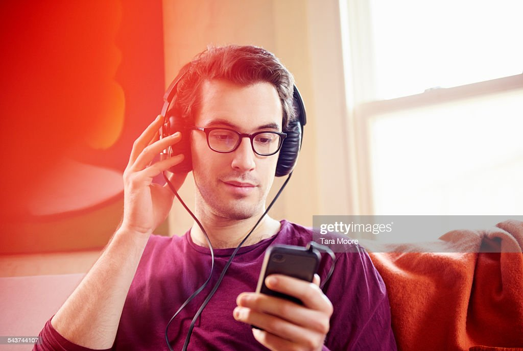 Young man with headphones and mobile at home : Stock Photo