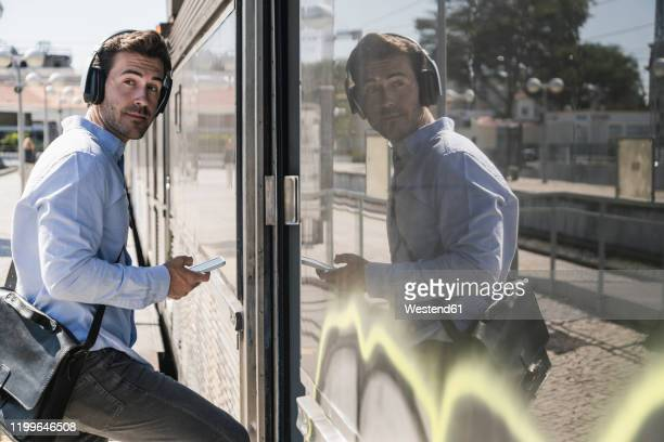 young man with headphones and smartphone entering a train - bahnreisender stock-fotos und bilder