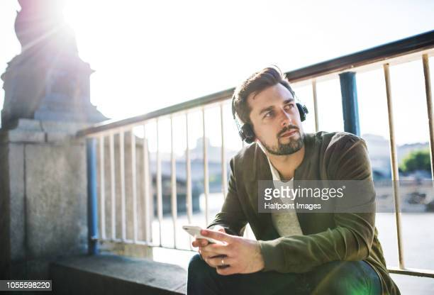 A young man with headphones and smartphone sitting on the bridge, listening to music.