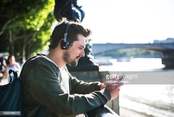 A young man with headphones and smartphone standing on a river promenade, listening to music.