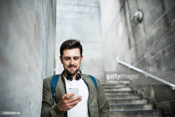 A young man with headphones and smartphone standing on the stairs, listening to music.