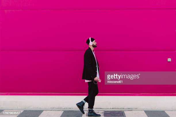 young man with headphones and smartphone walking along a pink wall - headphones stock pictures, royalty-free photos & images