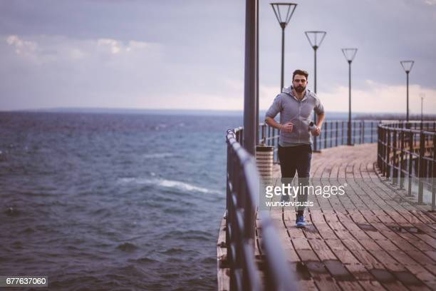 young man with headphones and water bottle running on jetty - pier stock pictures, royalty-free photos & images