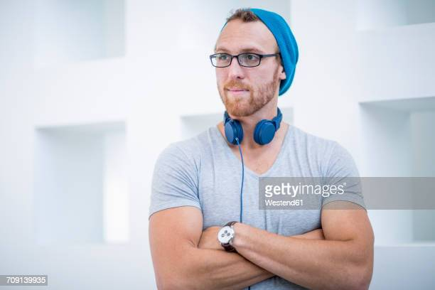 Young man with headphones around his neck looking away with arms crossed
