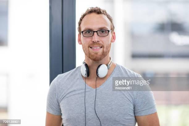 Young man with headphones around his neck, portrait
