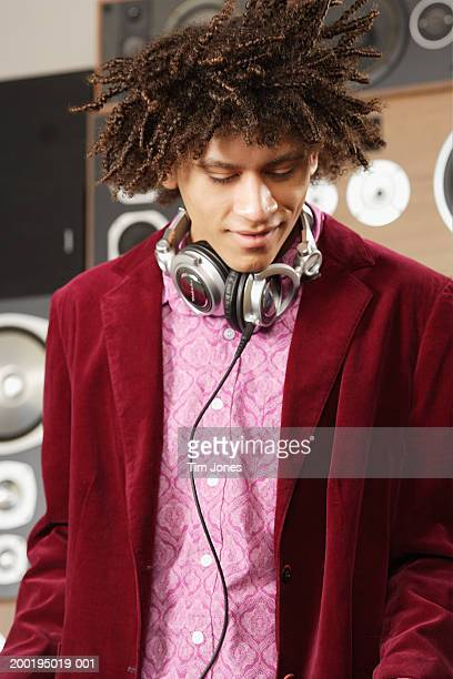 Young man with headphones around neck, shaking head