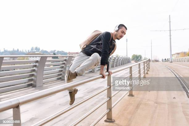 young man with headphones crossing a railing outdoors - parapetto barriera foto e immagini stock