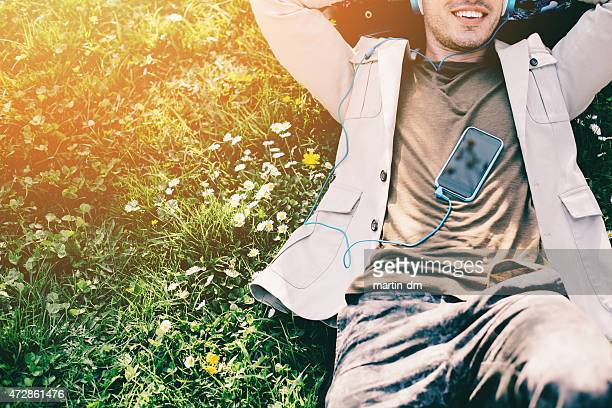 Young man with headphones lying down in the grass