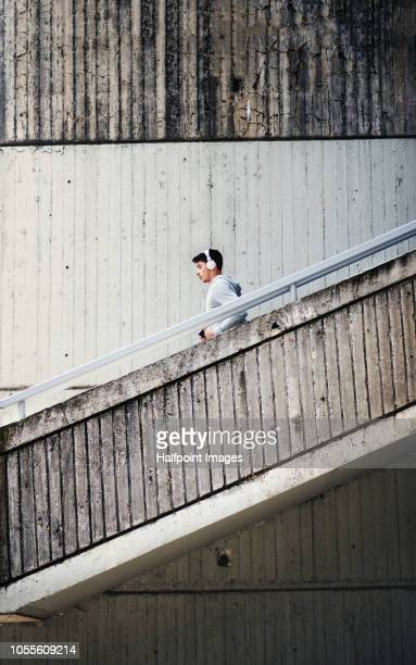 A young man with headphones running down the stairs, listening to music. Copy space.
