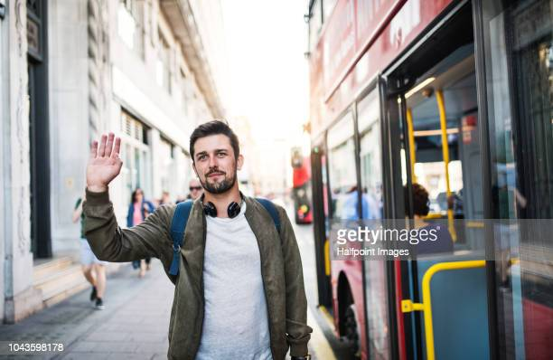 a young man with headphones standing on the bus stop, waving to somebody. - winken stock-fotos und bilder
