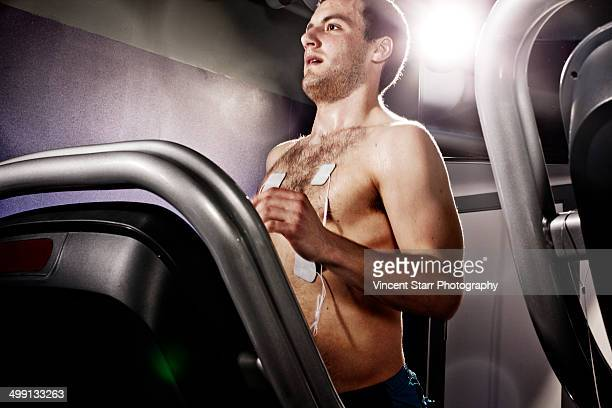 Young man with heart rate monitor on gym treadmill in altitude centre
