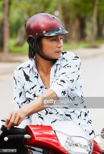 young man with helmet on motor scooter