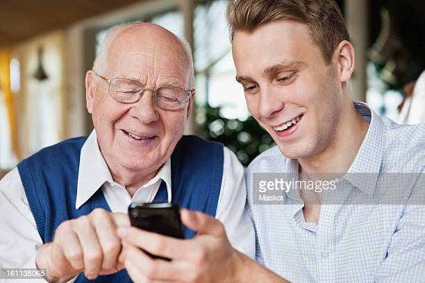 Young man with his father reading text message