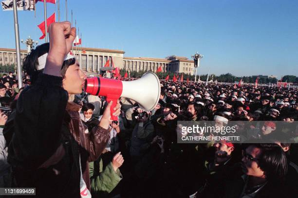 Young man with his fist raised uses a loudspeaker to adress students and local people gathered at Tiananmen Square in Beijing on May 14, 1989 after...