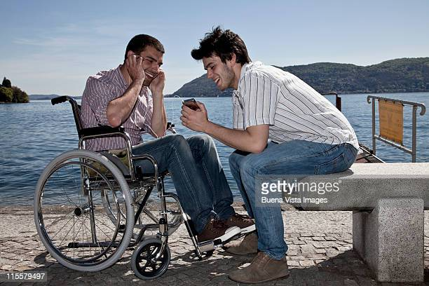young man with his friend in wheelchair - seulement des adultes photos et images de collection