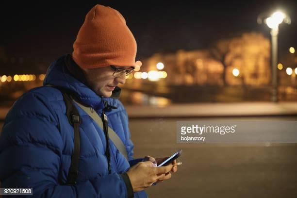 young man with his smart phone outside in the night city - mensagem com foto imagens e fotografias de stock