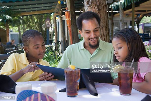 Young man with his son and daughter reading a menu at the breakfast table