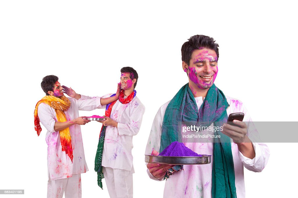 Young man with holi colour reading an sms : Stock Photo