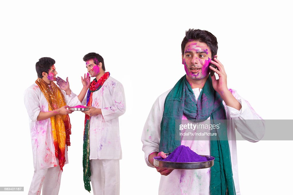 Young man with holi colour talking on a mobile phone : Stock Photo