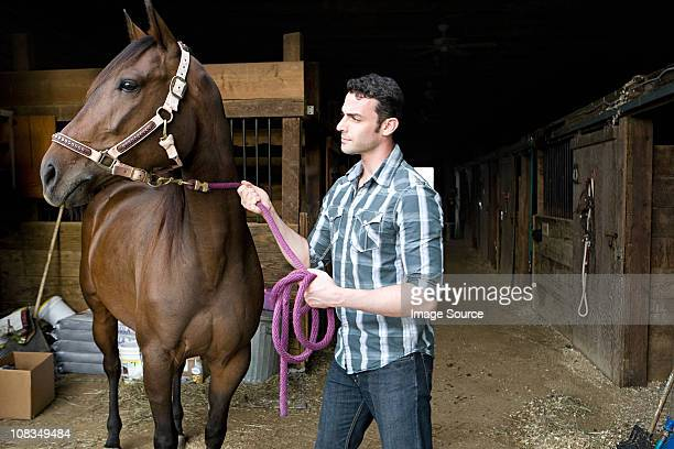 Young man with horse at stable