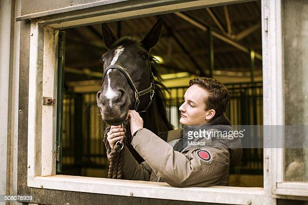 Young man with horse in stable