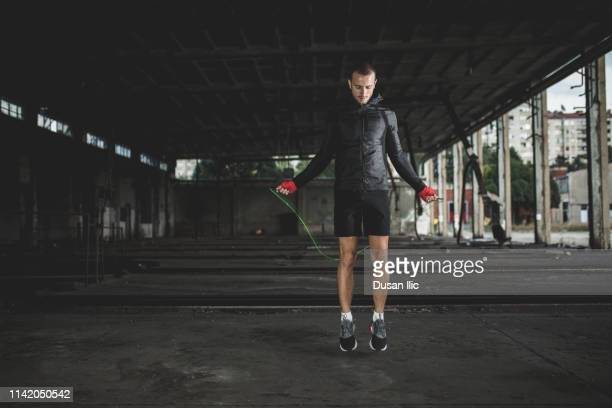 young man with jumping rope in garage - combat sport stock pictures, royalty-free photos & images