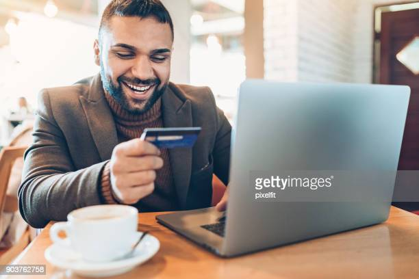 Young man with laptop and credit card in cafe