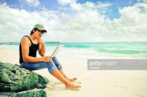 Young man with laptop by the sea