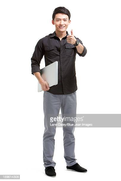 Young man with laptop doing thumbs up