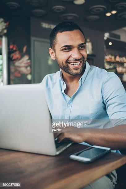 young man with laptop in cafe - midden oosterse etniciteit stockfoto's en -beelden