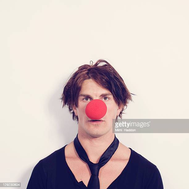 young man with large red clown nose - clown's nose stock photos and pictures