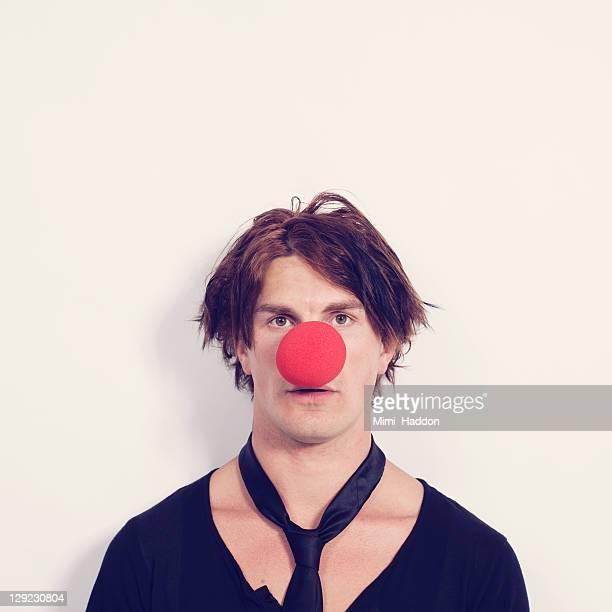 young man with large red clown nose - nariz de payaso fotografías e imágenes de stock