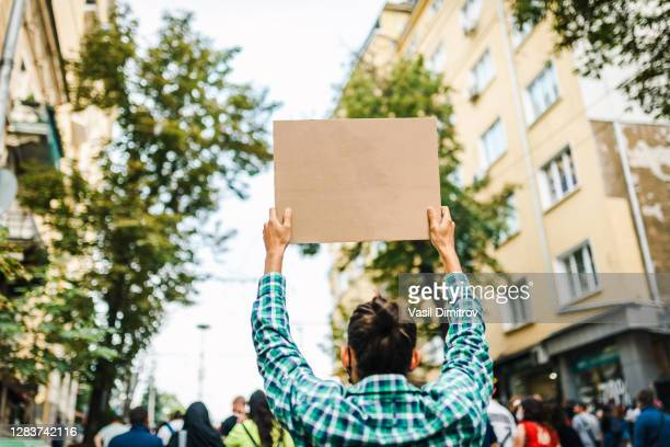 young man with long hair holding a blank poster in his hands. young activist / protester. human rights and social issues concept. - extremism stock pictures, royalty-free photos & images