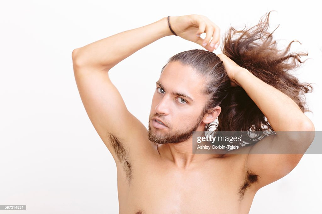 Young Man With Long Hair Putting In Ponytail Stock Photo
