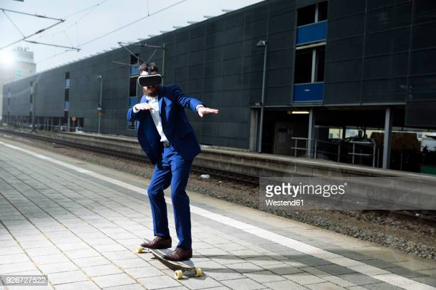 Young man with longboarding at train station, using VR glasses