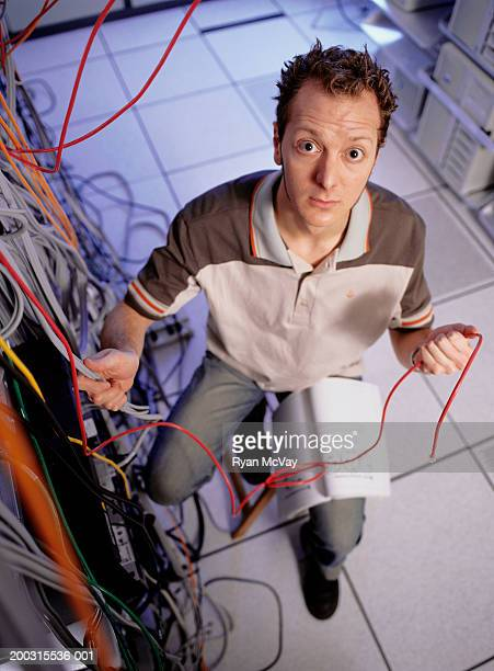 Young man with manual in computer room, checking wiring elevated view