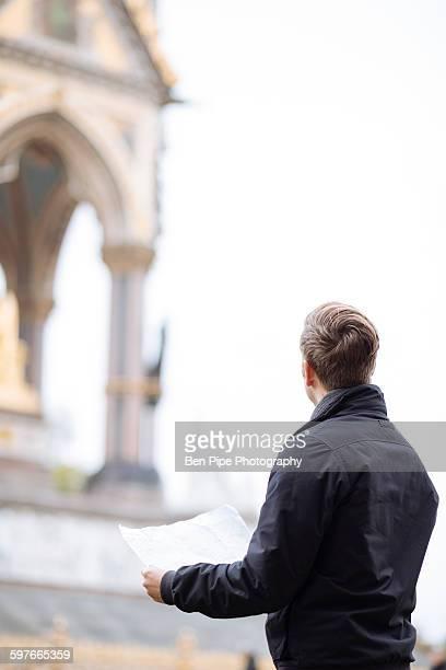 Young man with map looking up at Albert Memorial, London, England, UK