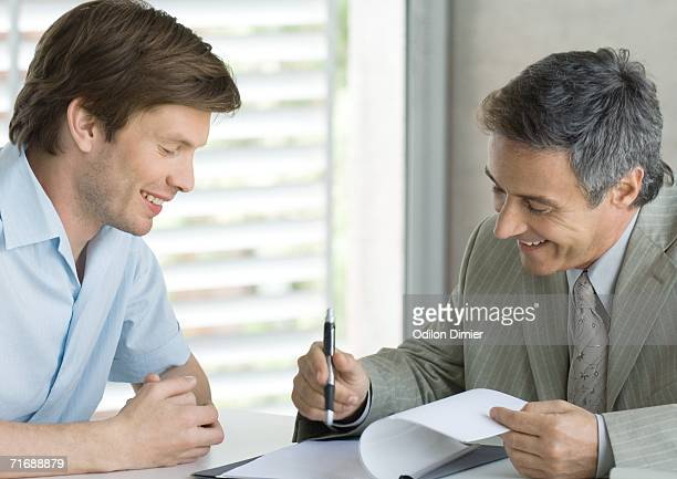 Young man with mature business man, looking at document