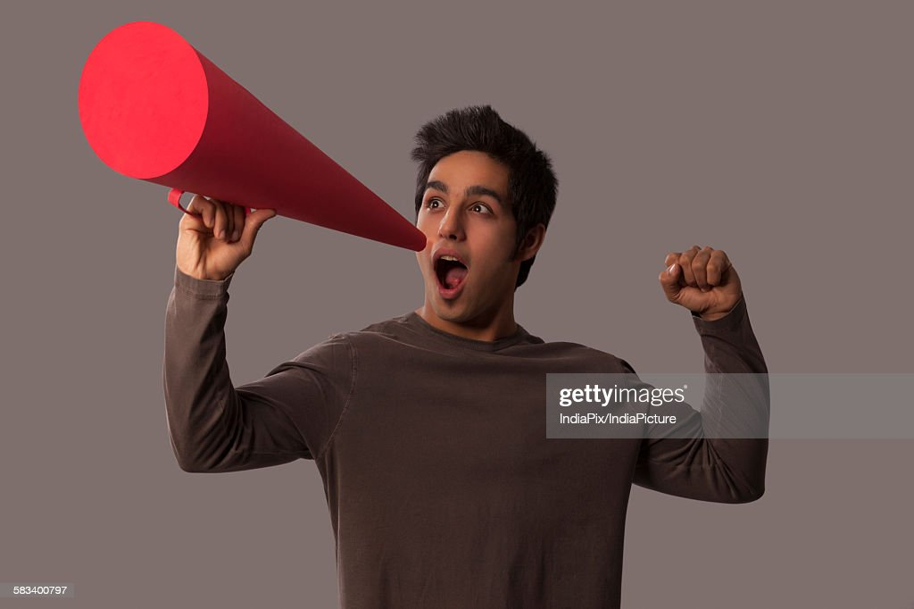 Young man with megaphone cheering : Stock Photo