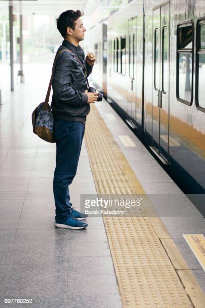 Young man with messenger bag waiting for train