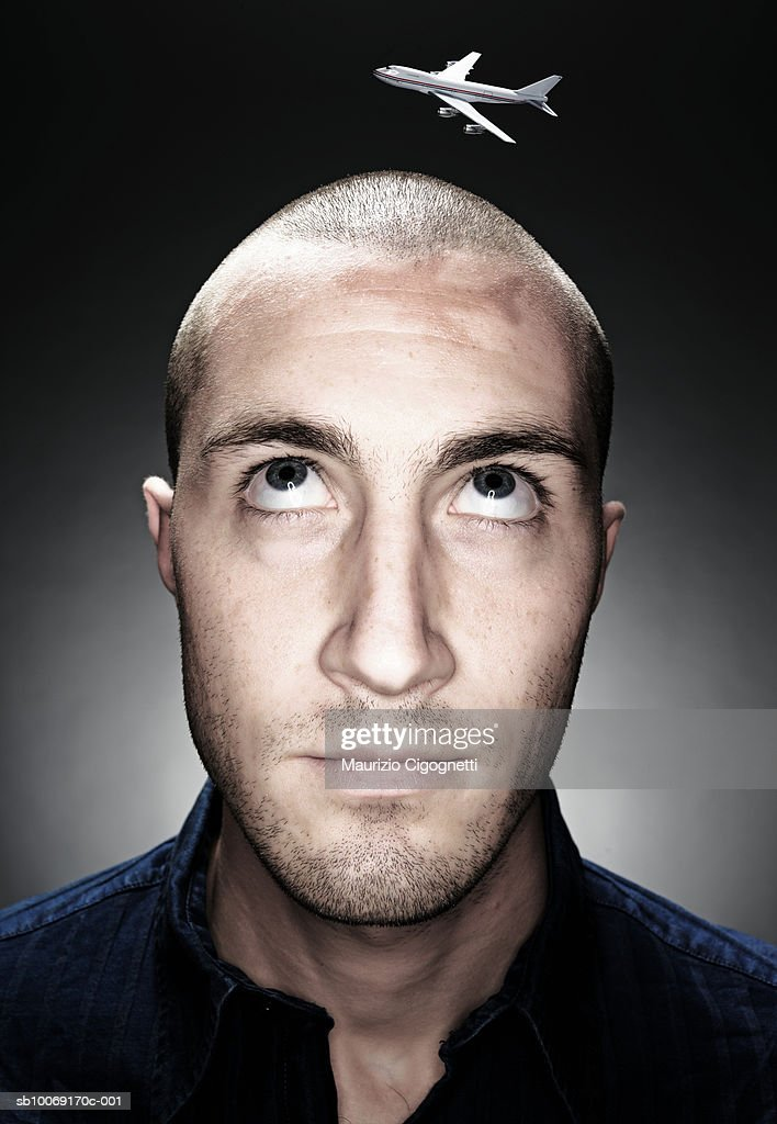 Young man with miniature airplane flying over head, close up, studio shot : Stockfoto