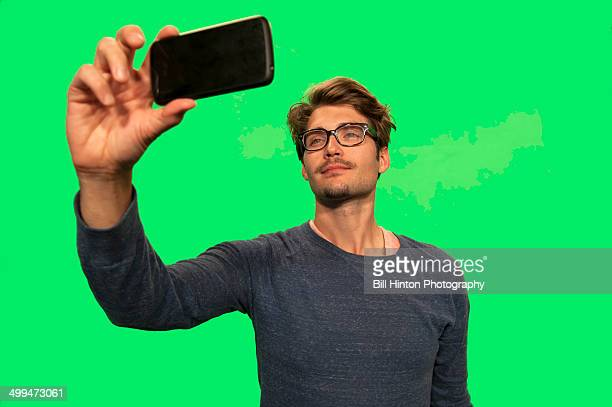 Young man with mobile camera taking selfie